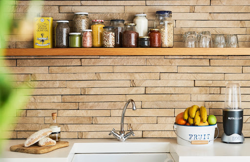 white countertop displaying blender, cutting board with bread, and a tin of fruit with a sink in front of a natural wooden backsplash and a wooden shelf with spices above